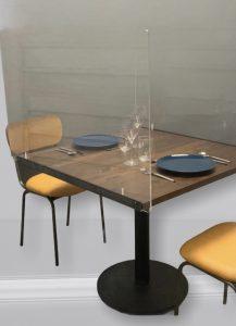 Mesa de un restaurante equipada con una mampara metacrilato para proteger del covid-19